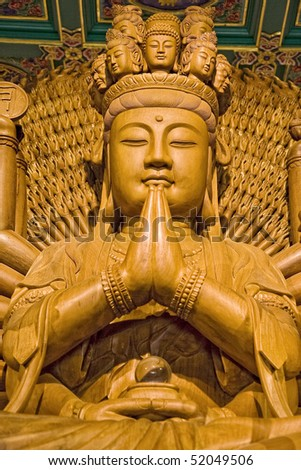 Wooden Buddha in a Chinese temple. - stock photo
