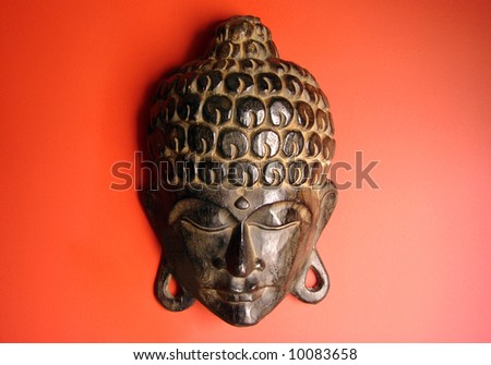 Wooden Buddha mask hanging from a red wall. - stock photo