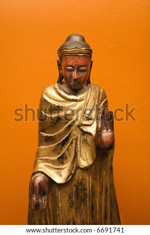 Wooden Buddha statue gesturing with one hand up and one hand down against orange wall.
