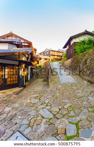 Wooden buildings on inclined stone path leads at south entrance of Magome post station on ancient Magome-Tsumago section of Nakasendo trail in Kiso Valley, Japan. Vertical