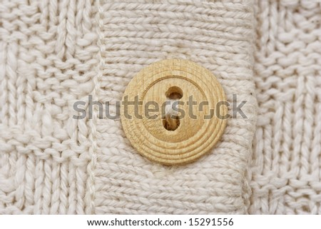 wooden button on knitwear - knitting pattern with purls and knits - stock photo