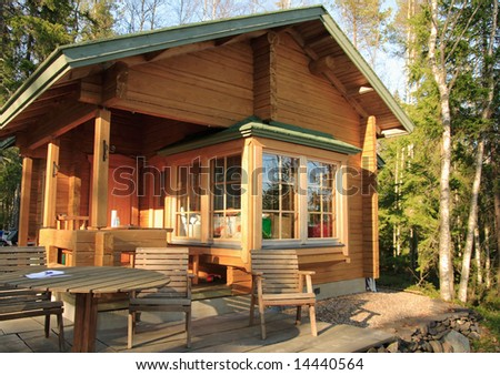 Wooden cabin with table and chairs on the terrace - stock photo