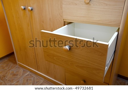 Wooden cabinet with open drawer - stock photo