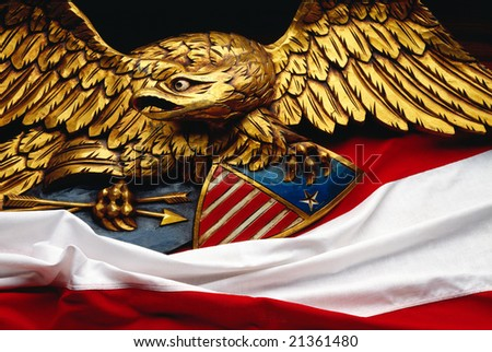 Wooden carved eagle with red and white bunting - stock photo