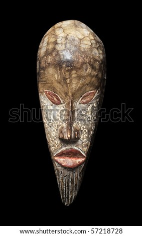 Wooden carved voodoo tiki mask isolated on a pitch black background. - stock photo