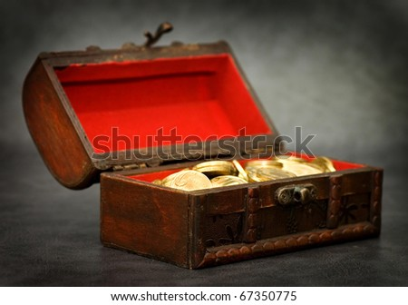 Wooden casket full of coins on grey background