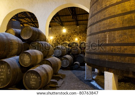 wooden casks of different sizes hold Port fortified wine to mature in wine cellars in Villa Nova de Gaia, Portugal