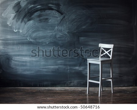 Wooden chair against a school desk for the letter. Impressive background - stock photo