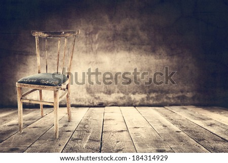 wooden chair and dark wall with shadows  - stock photo