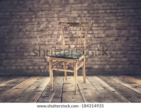wooden chair and wall of bricks