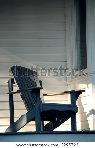 Wooden chair on a sunlit porch of a house - stock photo