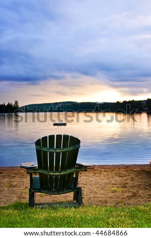 Wooden chair on beach of lake at sunset - stock photo