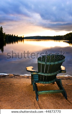 Wooden chair on beach of relaxing lake at sunset - stock photo