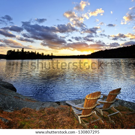Wooden chair on beach of relaxing lake at sunset in Algonquin Park, Canada - stock photo