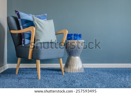 wooden chair with blue color pillow on carpet in living room - stock photo
