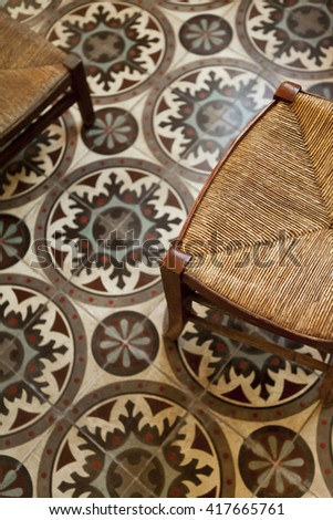 Wooden chairs and straws on a vintage tiles - stock photo