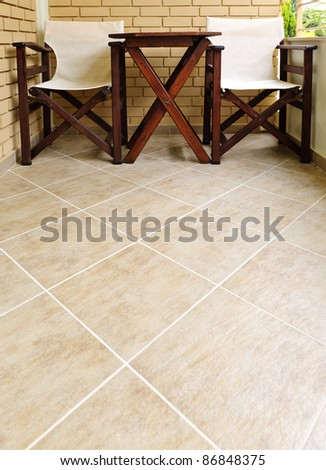 Wooden chairs and table on ceramic tile floor of balcony - stock photo