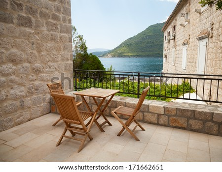Wooden chairs and table on open seaside terrace - stock photo