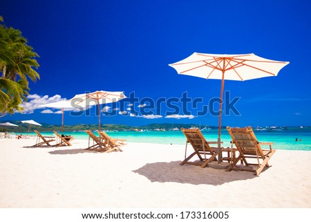 Wooden chairs and umbrellas on white sand beach facing the lagoon - stock photo