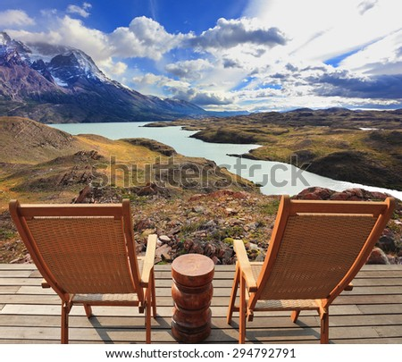 Wooden chairs in the Chilean national park Torres del Paine. Pleasant holiday - stock photo