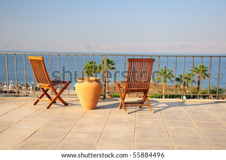 wooden chairs on a balcony with sea view - stock photo
