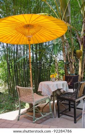 wooden chairs under umbrella in garden - stock photo