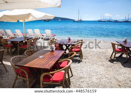 Wooden chairs with tables on the beach at seaside restaurant in Bodrum, Turkey