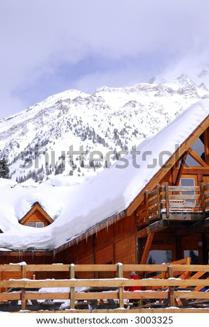 Wooden chalet at downhill ski resort with mountains in background - stock photo