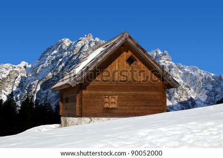 Wooden chalet in winter with snow-capped peaks - Alps Italy - stock photo