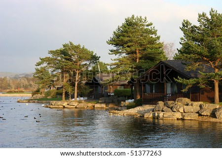 wooden chalets among the trees at the edge of a lake