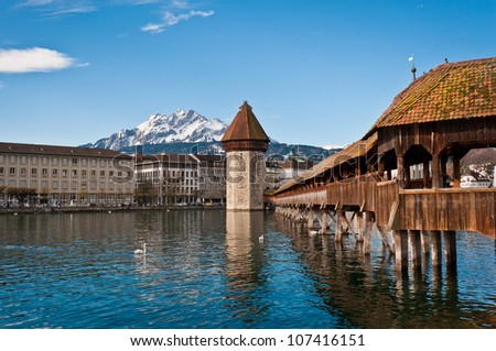 Wooden Chapel Bridge of Lucerne in Switzerland with tower - stock photo
