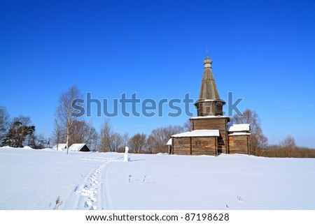 wooden chapel on snow field - stock photo