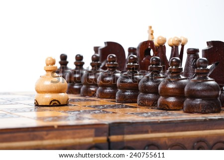 Wooden Chess Game with lonely and courageous pawn in front of enemies, white background, isolated,  - stock photo