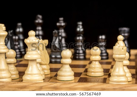 Wooden chess pieces on a game board ready to play