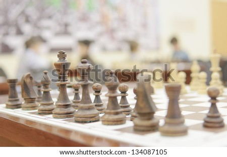 Wooden chess pieces on the Board and the boy playing in the background - stock photo