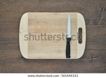 Wooden chopping board and knife - stock photo