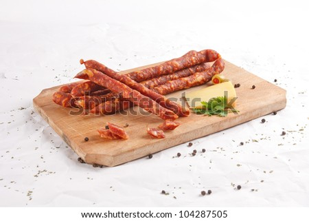 wooden chopping board with sausages, cheese and spices