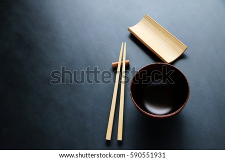 wooden Chopsticks and cups on blackboard Japanese and Chinese food equipment.Top view with copy space