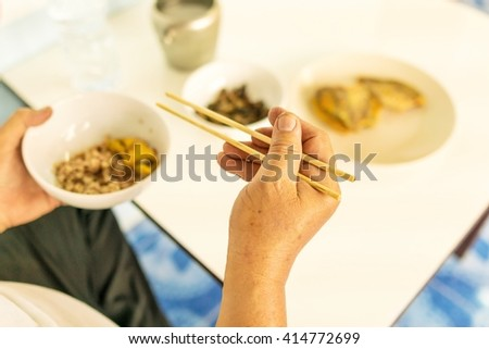 wooden chopsticks on right with brown rice in white bowl on left hand ; top view Breakfast (focus on right hand with chopsticks) Person 's right hand using bamboo chopsticks - stock photo