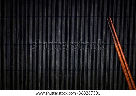 wooden chopsticks on the black bamboo mat background - stock photo