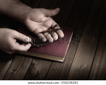 wooden Christian cross in his palms on the Bible during prayer. - stock photo
