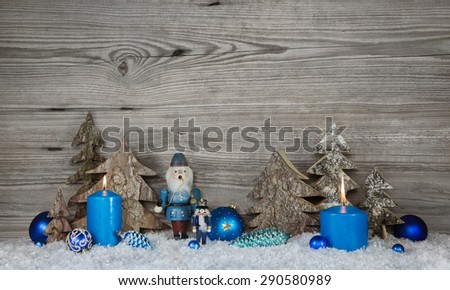 Wooden christmas background in grey with blue turquoise nutcrackers, snow and candles in country style decoration. - stock photo