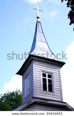 Wooden church tower with lighted cross on roof