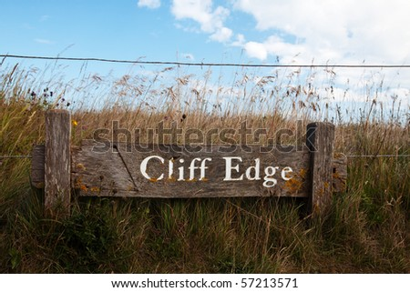 Wooden Cliff Edge warning sign at Beachy Head - stock photo