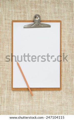 wooden clipboard on a old sackcloth background, with regular white blank paper. - stock photo