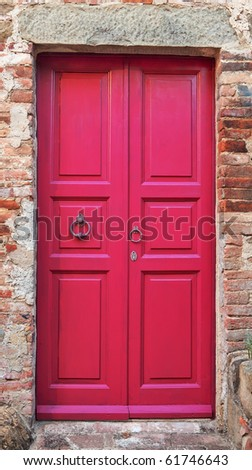 Wooden closed pink door with brick wall around it. - stock photo