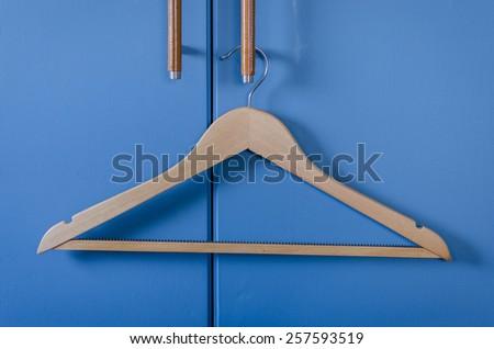 wooden cloth hanger hanging on door handle of blue wardrobe - stock photo