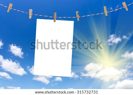 wooden clothes pin holding white sheets of photo paper on blue sky with sunlight. (paper side 3x2) - stock photo