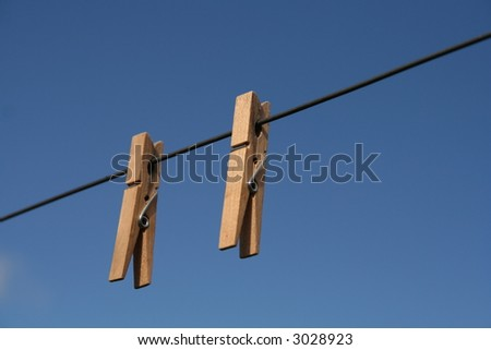 wooden clothespin on line against blue sky
