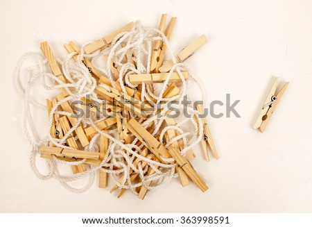 Wooden clothespins on a white rope and one clothespin isolated near them on light background. Washing and drying laundry at home. - stock photo